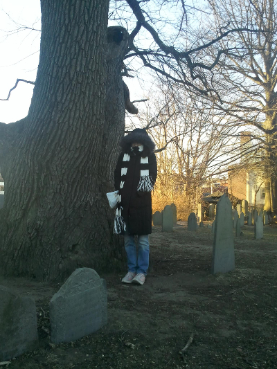 Julien in Salem, Massachusetts cemetery, with scarf and coat.